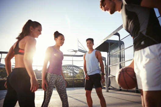 four young people in an outdoor basketball field
