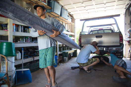 Two men working together under a pick-up truck in a garage with a man walking away from the working men while holding a covered outrigger canoe