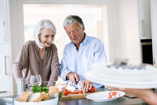 Senior couple preparing lunch at kitchen counter
