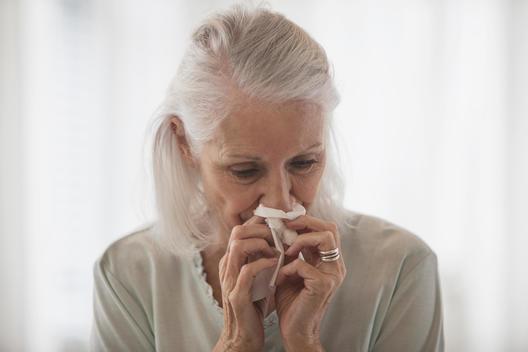 Senior Caucasian woman blowing her nose