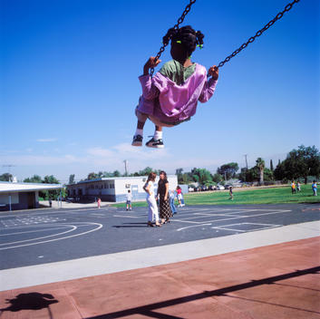 Student Swings During Recess As Two Teacher Chat At Coronita Elementary School