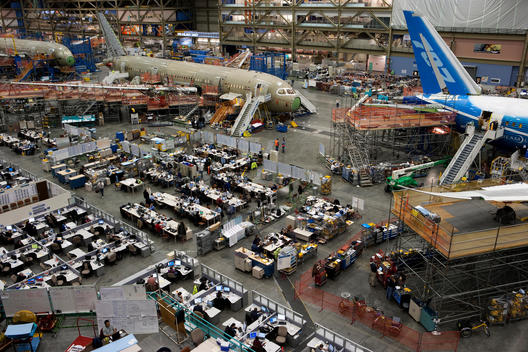 A view of the Boeing factory with its employees working on aircrafts in various stages of production