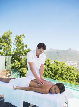 Woman receiving massage on spa patio