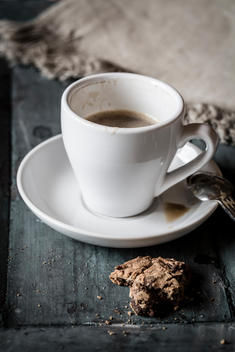 Cup of coffee and leftover of chocolate cookie on grey wood