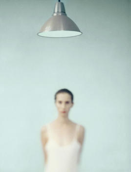 Young woman standing under lamp, focus on lamp in foreground