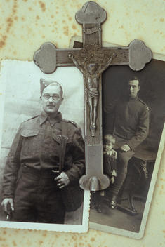 Vintage black and white photos of man in World War 2 army uniform and as young boy with uniformed father lying with grey metal crucifix