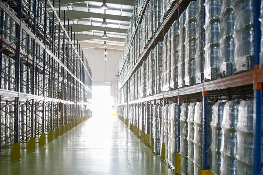 Pallets of water bottles on warehouse shelves