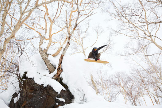 A man jumping off a cliff snowboarding