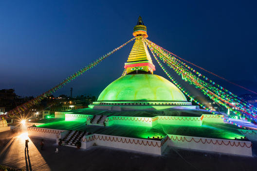 Prayer flags hanging from Boudhanath Stupa temple spire illuminated at night, Kathmandu, Kathmandu Valley, Nepal