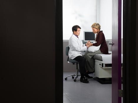 Doctor examines patient in an exam room.