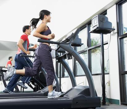 People running on treadmills at health club