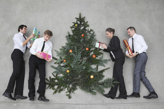 Four business people with Christmas presents standing round Christmas tree, elevated view