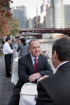 Two Business Men Talk At An Outdoor Patio Next To The Chicago River.