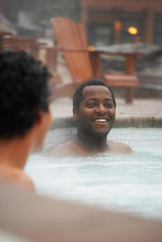 Two multi-ethnic men sitting in hot tub