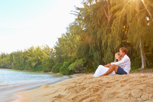 Caucasian couple sitting on tropical beach