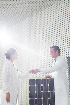 Scientists handshaking at solar panel in laboratory