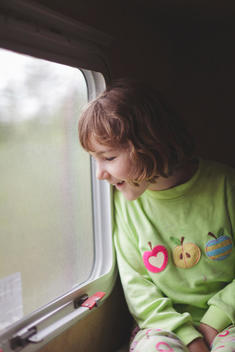 Caucasian girl looking out train window