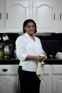 Portrait Of A Housekeeper Doing The Dishes