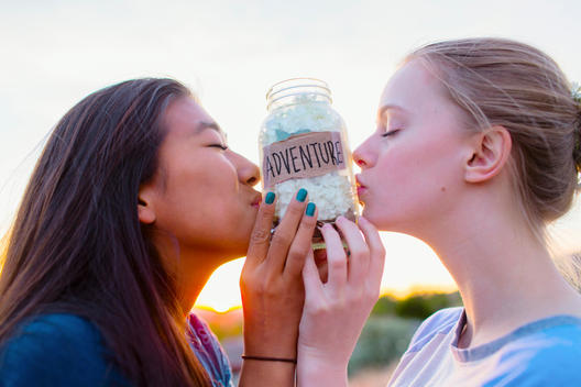 Teenage girls kissing adventure savings jar