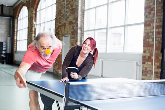 Young woman and senior man playing table tennis in health club