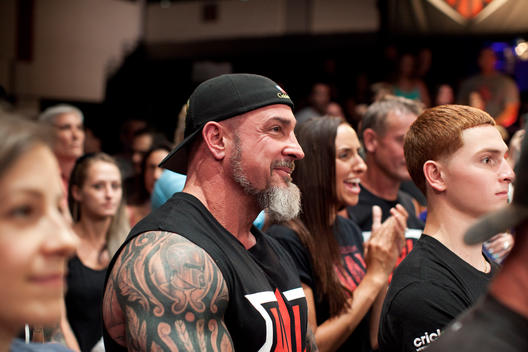 Audience members smile and cheer at the arm wrestling competition in Las Vegas