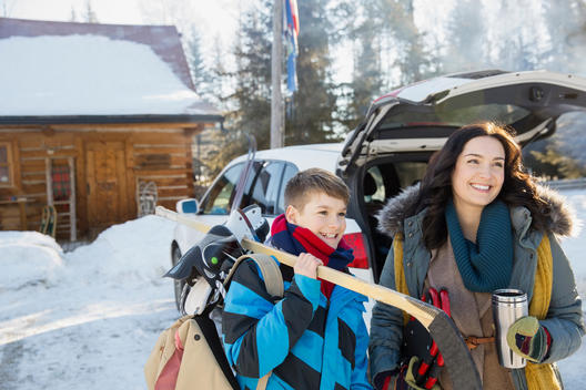 Mother and son standing outdoors with winter sports gear