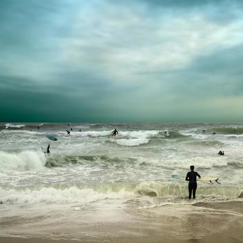 People surfing in stormy ocean