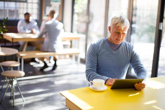 Older man using digital tablet in cafe