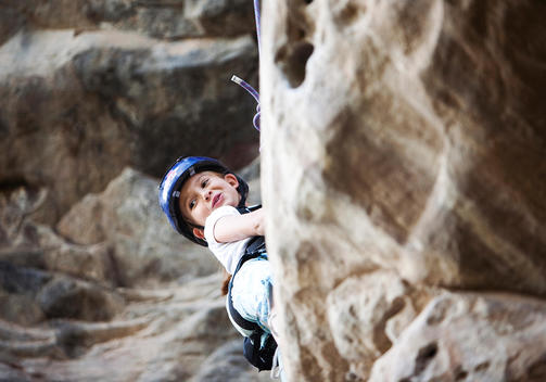 A young girl wearing a rock climbing helmet, looks out from the rock as she sets out to climb a sport route at Santa Clara in Ecuador.