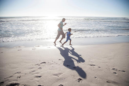 Mixed race father and son running on beach