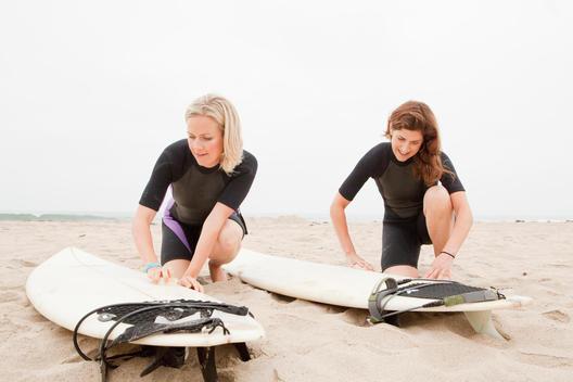 Caucasian women preparing to go surfing