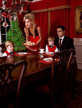 Fashion Portrait Of Family In Formal Dress Attire At Dining Room Table During Christmas