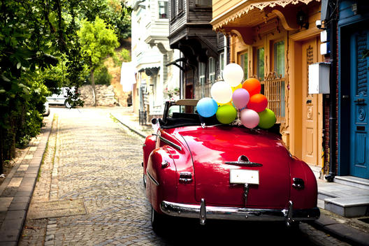 Classical Car Decorated for A Wedding with colorful balloons for a photo shooting.