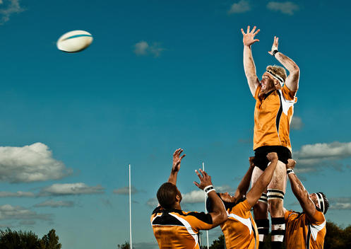 Rugby Player Leaping Up To Catch Ball