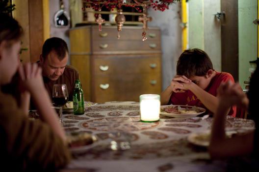 Family Prays At Christmas Dinner
