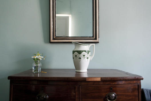 Detail of a French country cottage bedroom. Chest of drawers with vase and small flower pot