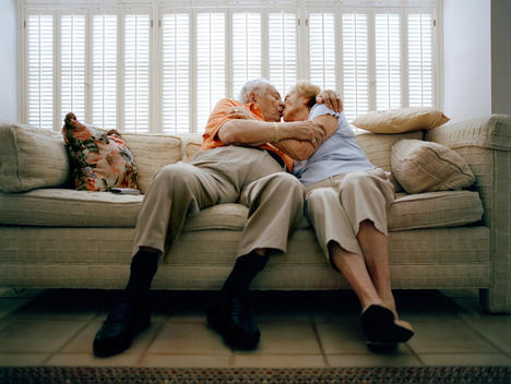 Senior Couple Kissing On A Couch In Florida.