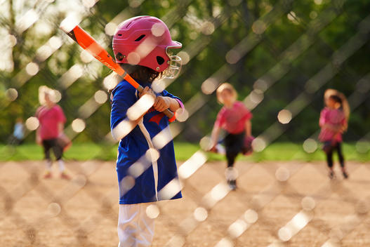 girl with kids softball bat behing protection net playing softball waiting for the ball
