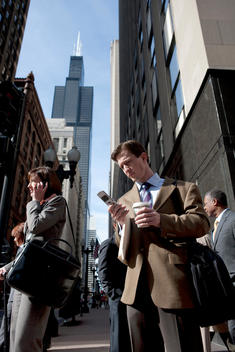 A Business Man Checks His Cell Phone At A Busy Chicago Street Corner.