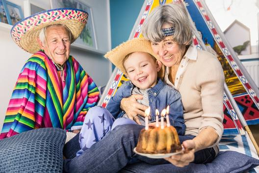 Senior couple and grandson celebrating with birthday cake on living room floor