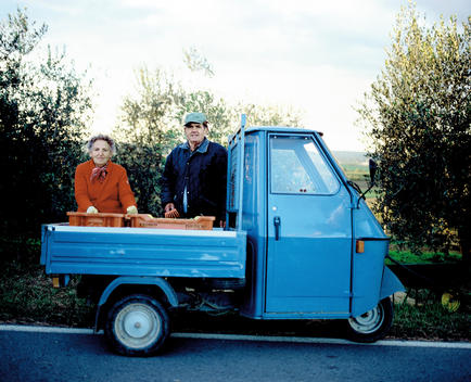 Senior Couple Farmers Standing Behind A Small Truck By Olive Trees.