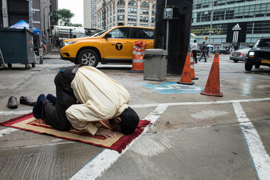A Muslim taxi driver performs a prayer at a gas station.