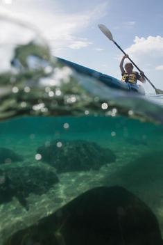 underwater view of boy paddling ocean kayak\'