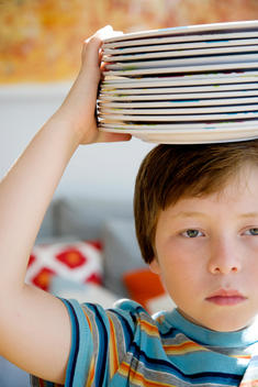 Child carrying stacked dishes