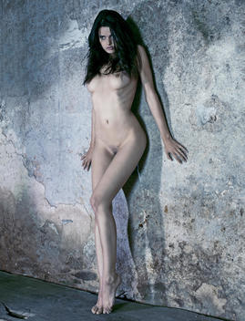 Nude woman posing against wall