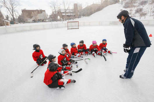 Coach discussing with players on ice hockey rink