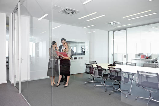 Business people standing in conference room looking at book
