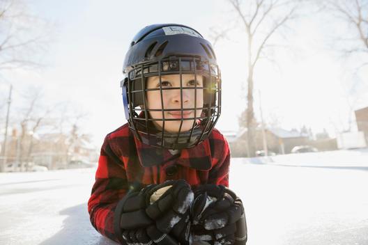 Boy lying on ice hockey rink