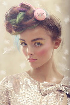 Beauty shot of a young caucasian girl, wearing a sequin top, hair up with a bird sitting on her multicolor bun. Looking in the lens
