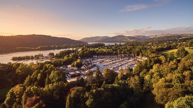 Panoramic view of Lake Windermere in the Lake District and resort zone in green trees on background of sunset in mountains.